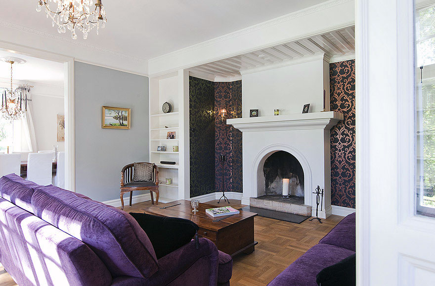 Warm Living Room with Purple Sofa and Fireplace Mantels