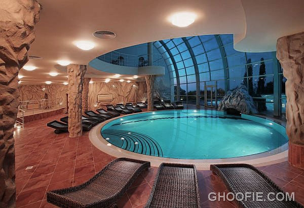 Fabulous Rounded Indoor Swimming Pool Design with Rattan Lounge Chairs