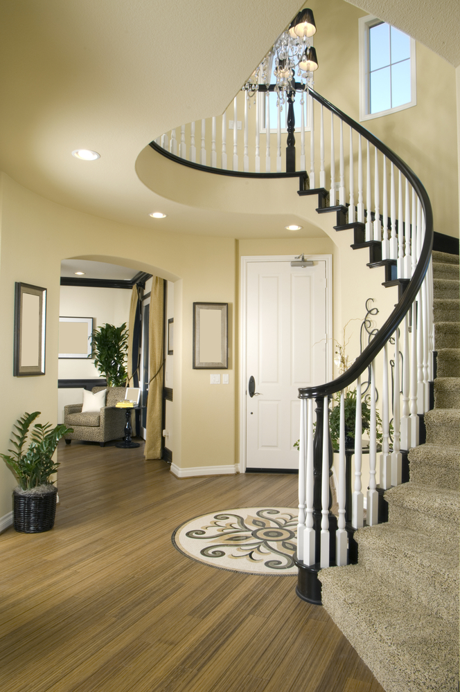 Modern Foyer With Stairs : Modern entry way with wood floor and winding stairs