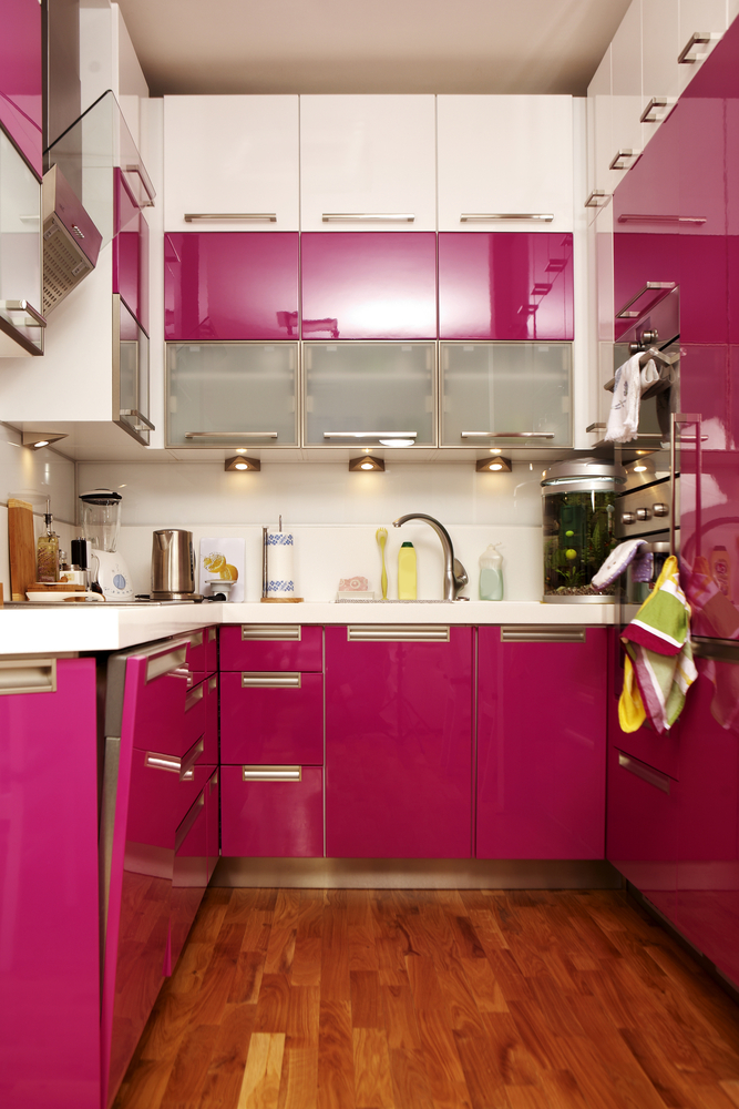 Pink kitchen cabinets with wood floor