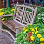 Wood backyard bench in flowers